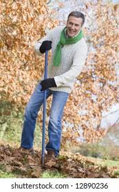 Senior man tidying autumn leaves in garden