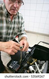 A senior man with a toolbox