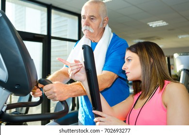 senior man training in the gym with a personal trainer