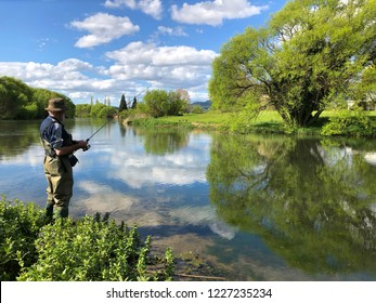 A senior man trout fishing during this spring scene with a perfect reflection of blue skies and a large green tree on the Rangitaiki River, New Zealand. Horizontal