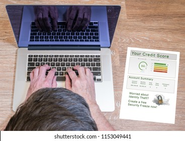Senior man typing on laptop with a credit report and credit freeze option on desk