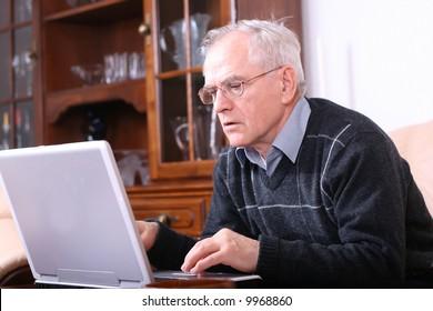 Senior man typing on a laptop