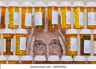 Senior man with an unhappy, depressed expression and his hands framing his face looking through an opening in rows of prescription medication. Health care cost can overwhelm many senior citizens.