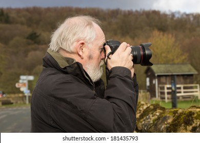 senior man using camera outdoors