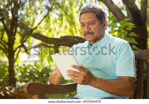 Senior man using digital tablet in the garden