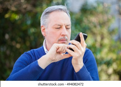 Senior man using his cell phone outdoors