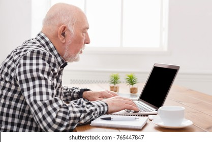 Senior man using laptop with blank screen back view, mockup. Mature male making video call with computer at home, copy space