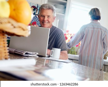 Senior man using laptop at breakfast table in kitchen at camera