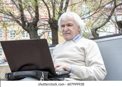 Senior man using laptop computer at rest in the park outdoors