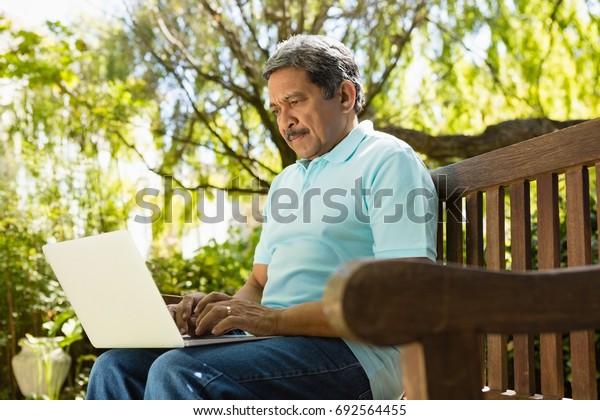 Senior man using laptop in the garden