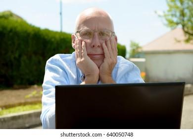 A senior man using a laptop outside