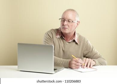 Senior man using laptop whilst taking notes
