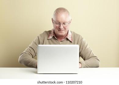 Senior man using laptop whilst smiling