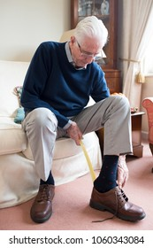 Senior Man Using Long Handled Shoe Horn To Put On Shoes