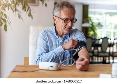 Senior man, der ein medizinisches Gerät verwendet, um den Blutdruck zu messen