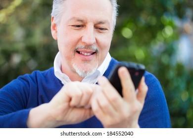 Senior man using a smartphone outdoor