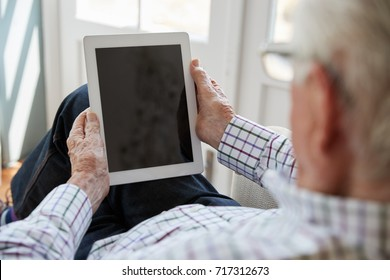 Senior man using tablet computer at home, over shoulder view