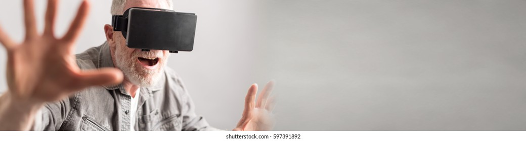 Senior man using virtual reality headset