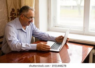 Senior Man Video Conferencing On Laptop Over Wooden Desk