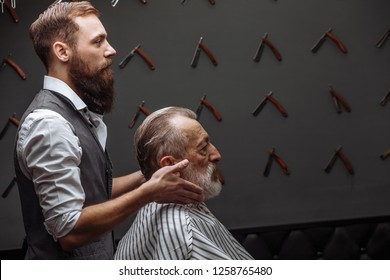 Senior man visiting hairstylist in barber shop. Close up of professional groomed barber trimming senior client grey hair with razor. Man s Beauty Salon, Barbershop Concept.