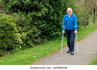 Senior man walking with crutches in park, looking happy, walking toward camera
