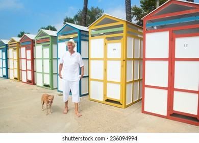 Senior man walking the dog at beach with colorful wooden huts