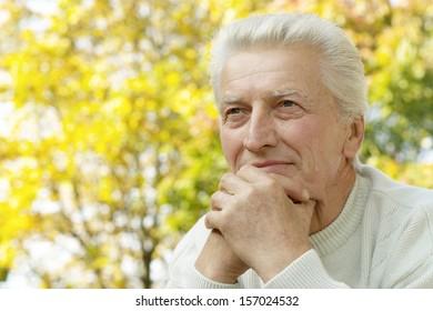 Senior man walking in the park in autumn