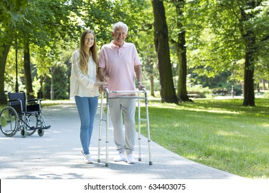 Senior man walking in the park with walking frame accompanied by his caregiver