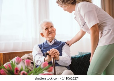 Senior man with a walking stick being comforted by nurse in the hospice - Shutterstock ID 1410616274
