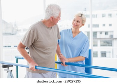 Senior man walking with therapist help in fitness studio