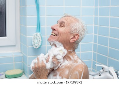 Senior man washing his body with soap in bath.