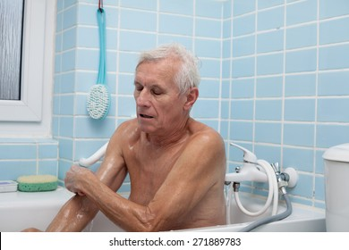 Senior man washing his body with soap sponge in bath.