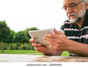 Senior man watching TV on his new tablet PC in the park.