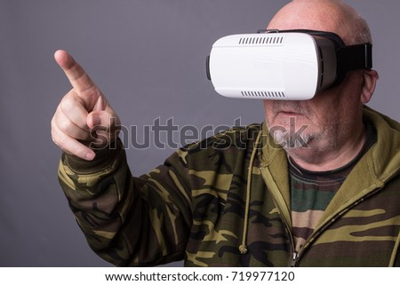 81985c2c7ff Senior man in wearable technology VR glasses. Confident old man wearing  camouflage clothing in virtual