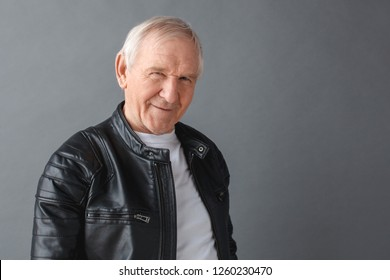 Senior man wearing black leather jacket standing isolated on gray wall looking camera smiling playful close-up