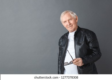 Senior man wearing black leather jacket standing isolated on gray wall holding sunglasses looking camera cool