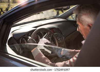 Senior man wearing black protective gloves disinfecting the inside of a car with antibacterial wet wipes.