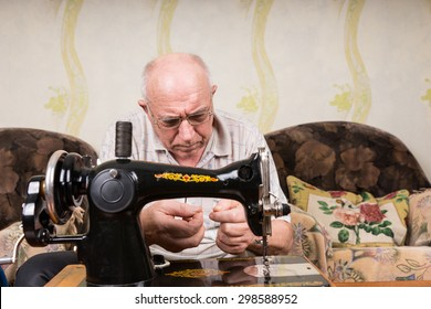 Senior Man Wearing Eyeglasses in Deep Concentration Threading Needle of Old Fashioned Manual Sewing Machine at Home in Living Room