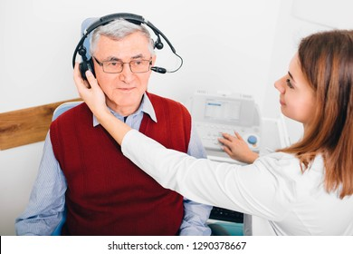 Senior man wearing headphones, sitting near audiologist during ear exam at hearing clinic