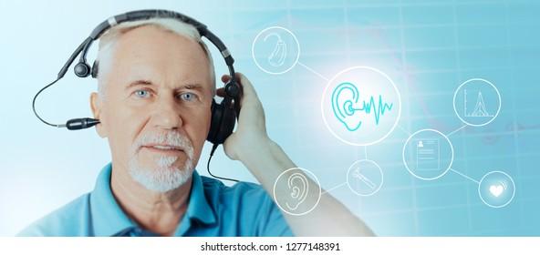 Senior man wearing headphones while audiometry test. hearing icons on background