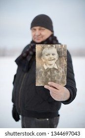 Senior man wearing knit cap, scarf, jacket and leather gloves smiling and showing his picture as child standing in winter field - memory concept, focus on picture