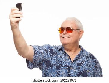 Senior man wearing loud hawaiian shirt on white background taking photo selfie with mobile phone.