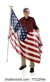 A senior man wearing a stars and stripes cap while carrying a large American flag.  Isolated on white.