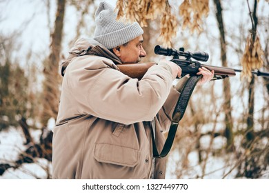 Senior man wearing stylish winter clothes walking with .22 scoped rifle in a forest on alert