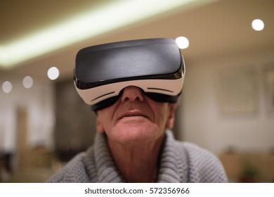 Senior man wearing virtual reality goggles at home