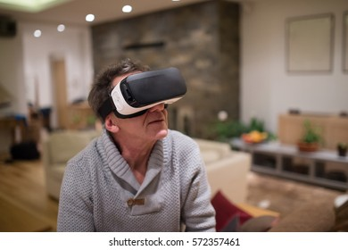 Senior man wearing virtual reality goggles at home