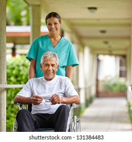 Senior man in wheelchair with nurse on a stroll through the hospital garden
