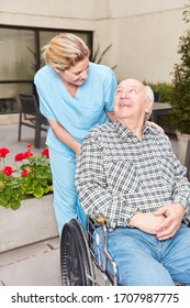 Senior man in wheelchair in rehab clinic and caring geriatric nurse