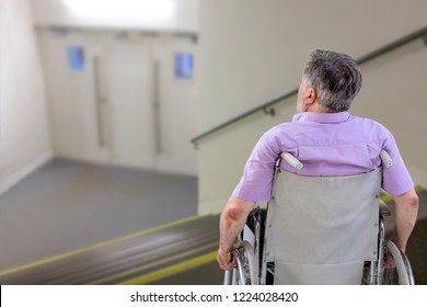 senior man in a wheelchair at the top of steps