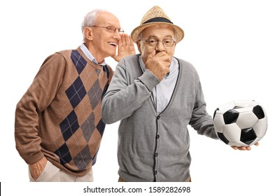Senior man whispering to friend holding a deflated soccer ball and laughing isolated on white background